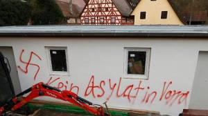 """Brandanschlag auf Asylantenheime in Vorra bei Nürnberg, selbstverständlich wurde sofort ein schriftliches Bekenntnis auf einer Hauswand hinterlassen, natürlich mit Hakenkreuz. Allerdings deutet die Schreibweise eher auf eine Täterschaft aus dem Bereicherungs-Umfeld hin, die in Diensten des Verfassungsschutzes Straftaten verübt. """"Kein Asylat in Vorra"""", steht auf der Wand. Kaum möglich, dass das von einem Deutschen geschrieben wurde. Deutsche Täter hätten geschrieben: """"Keine Asylanten in Vorra""""."""